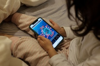 Life inside a red zone: 2-year-old Bianca Toniolo looks on a phone at an illustration of a microscopic view of the new coronavirus, which she says looks like the sun,  at home on a rainy day in San Fiorano, one of the towns in northern Italy on lockdown due to a coronavirus outbreak, in this picture taken by her father Marzio, March 2, 2020. Picture taken March 2, 2020. Marzio Toniolo/via REUTERS THIS IMAGE HAS BEEN SUPPLIED BY A THIRD PARTY. MANDATORY CREDIT